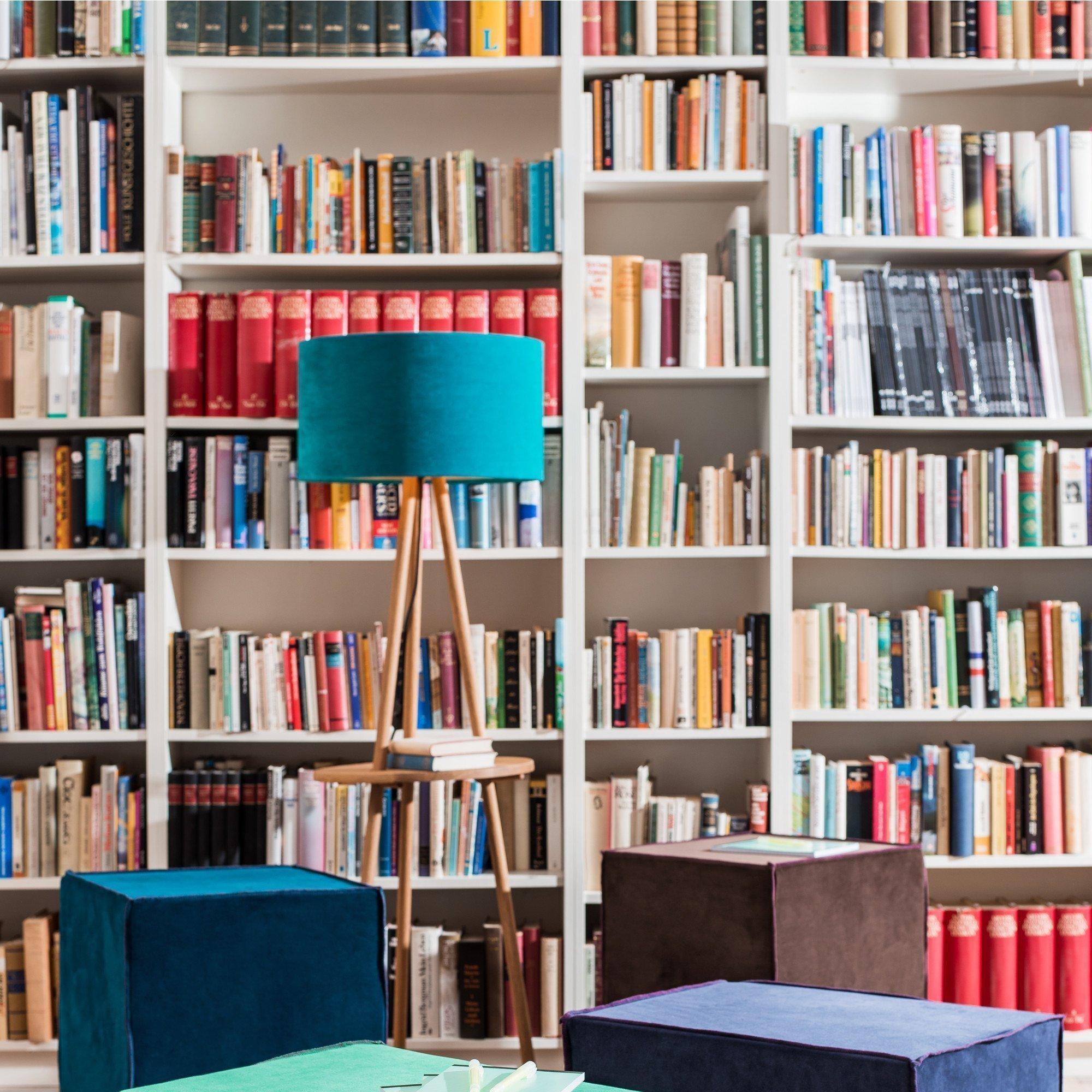 Dreibein Stehleuchte vor einem Bücherregal
